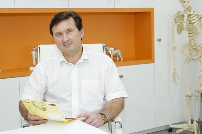 Orthopäde in seinem Sprechzimmer mit Patientenakte