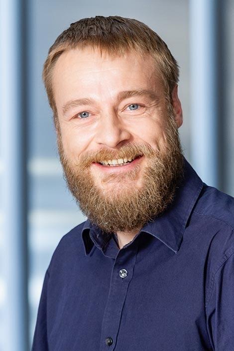 freundliches Bewerbungsfoto eines Mann mit Bart